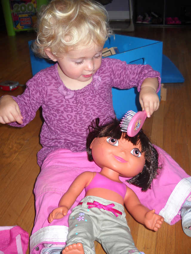 Girl brushing doll's hair